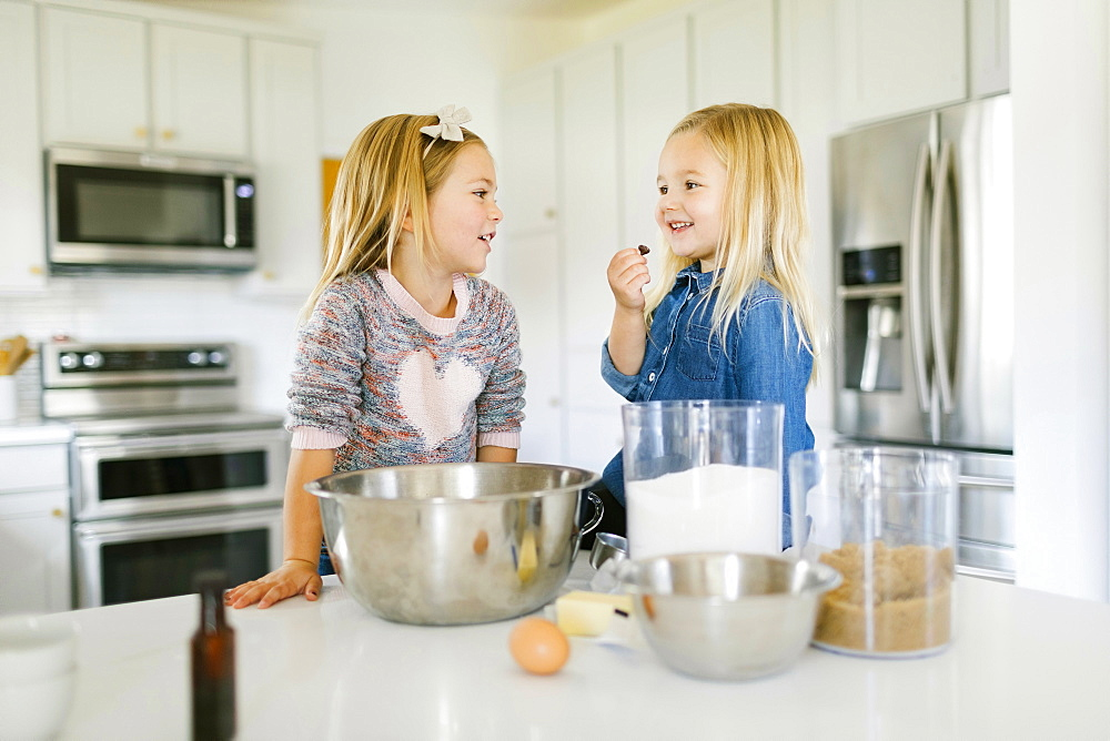 Smiling girls baking cookies