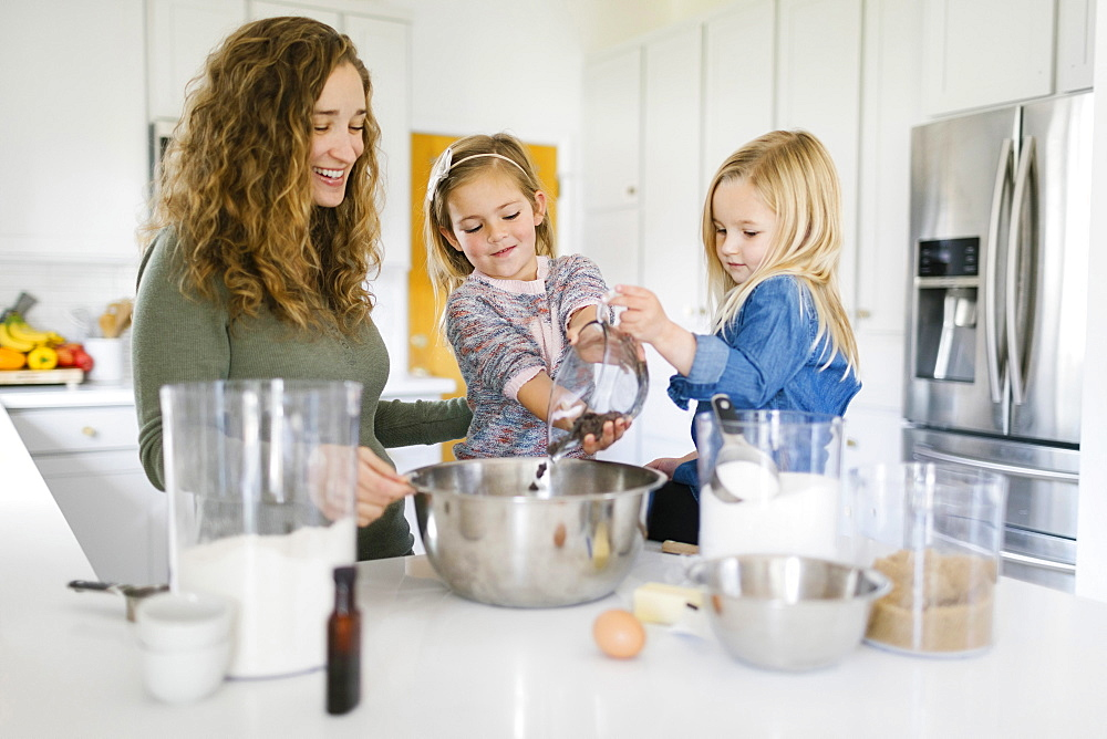 Woman baking cookies with her daughters