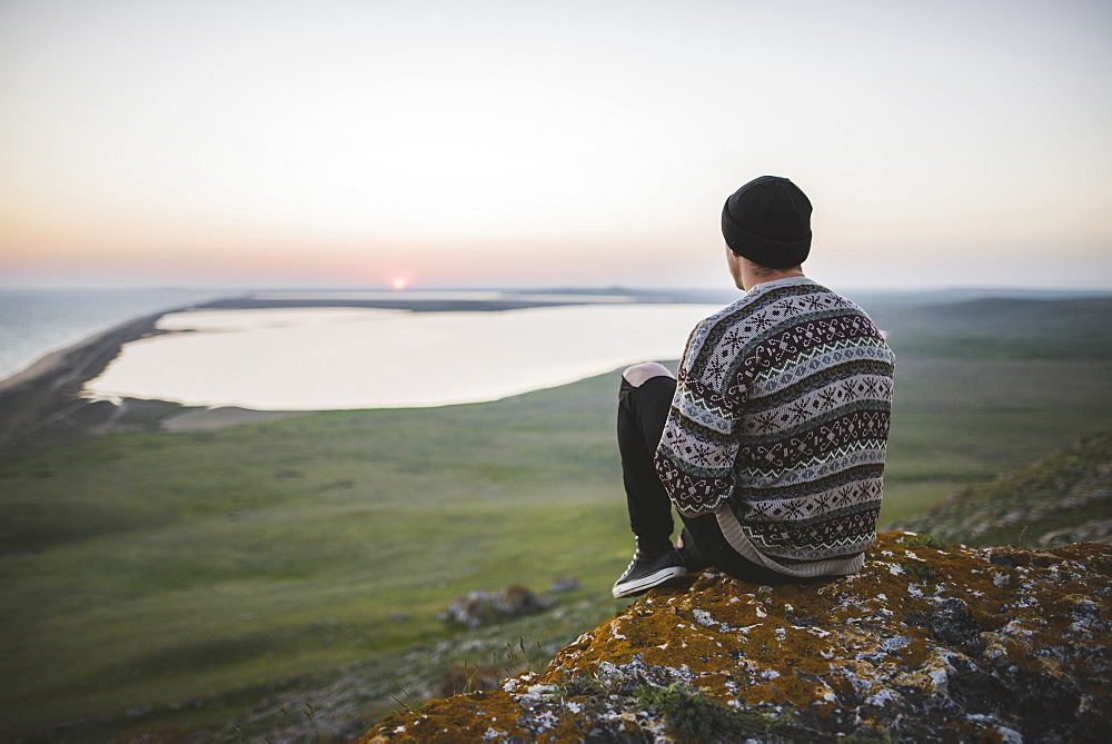 Young man in striped sweater sitting on hill during sunset