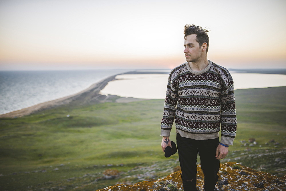 Young man in striped sweater on hill during sunset