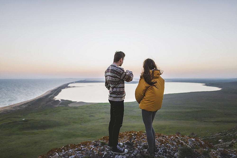 Young couple standing on hill at sunset