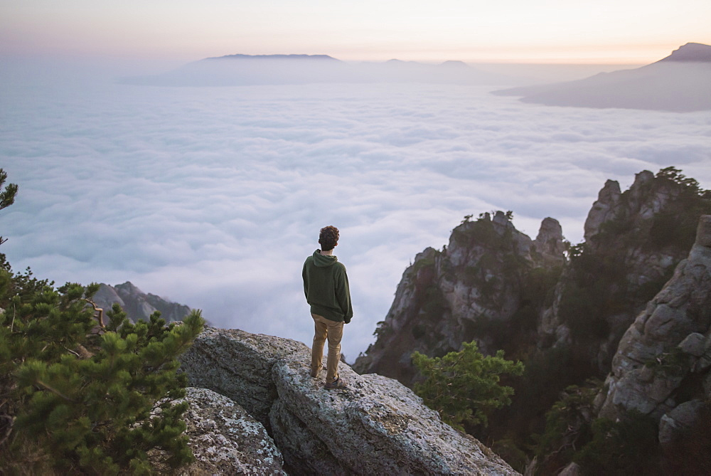 Young man standing on mountain above fog - 1178-28648