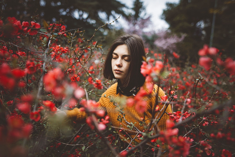 Young woman with eyes closed in shrubs with red flowers