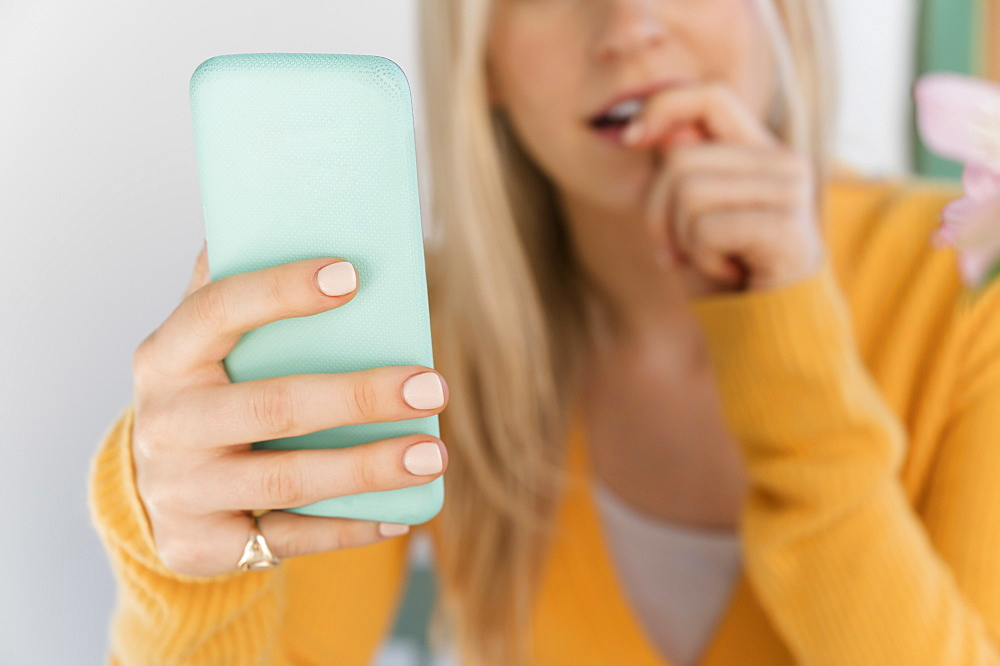 Woman holding smartphone and biting nails