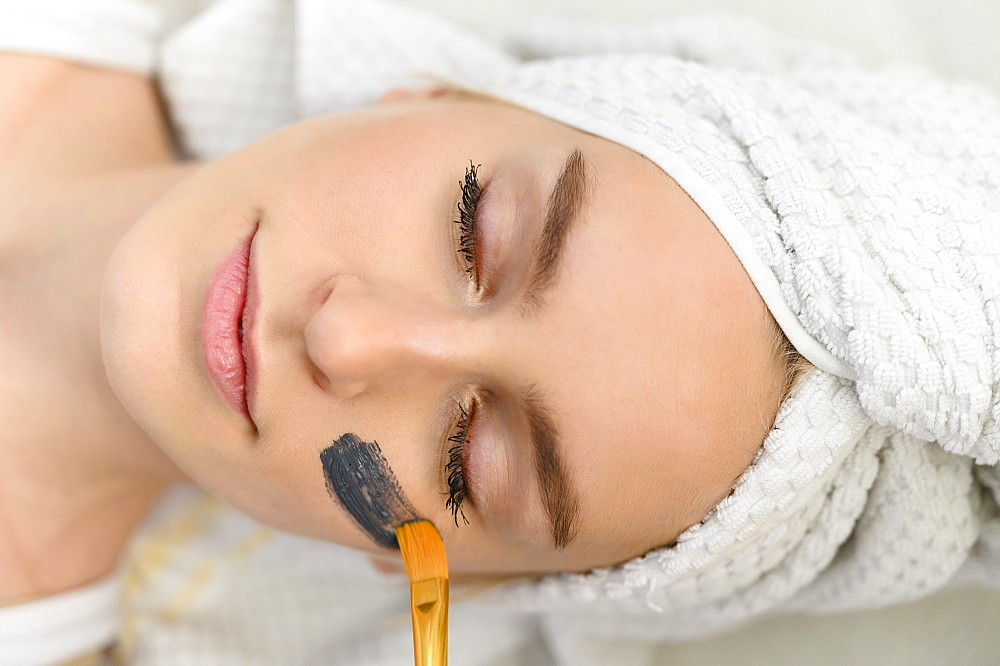 Face mask being applied on woman's face at spa