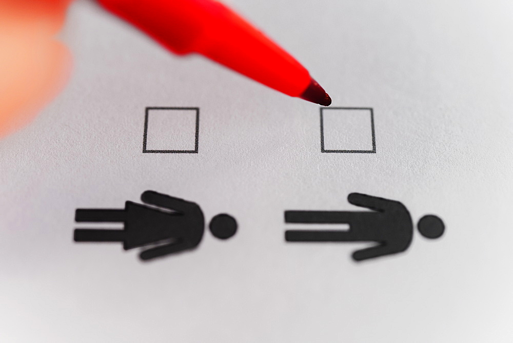 Person marking with pen on male and female gender checklist