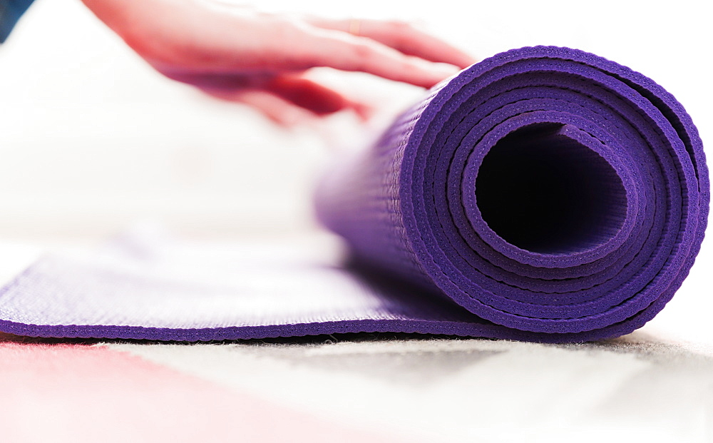 Woman's hand rolling yoga mat