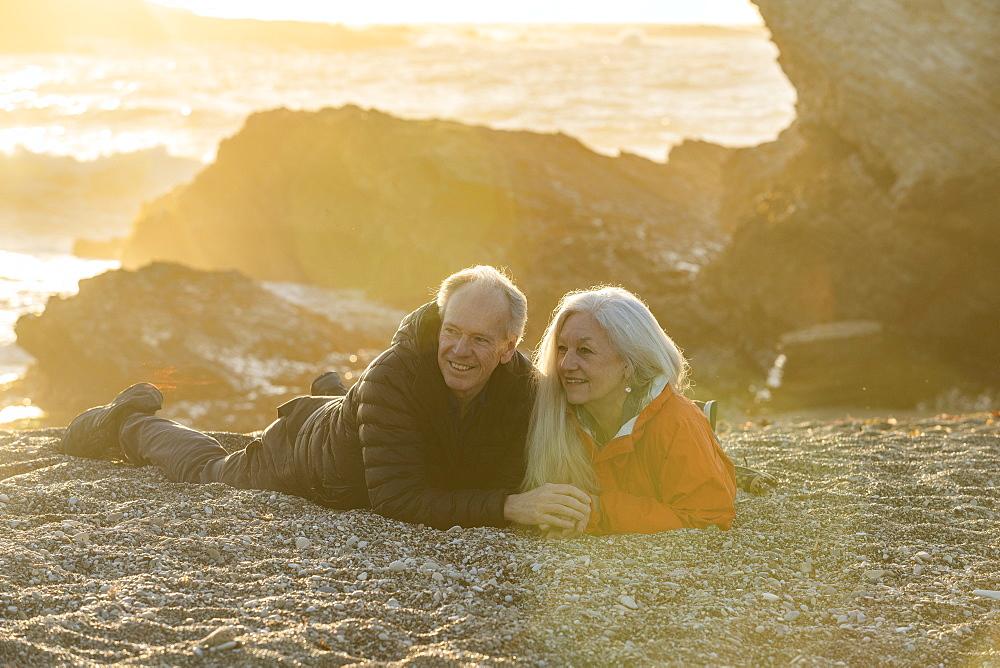 Seniorcouple enjoying sunset on beach