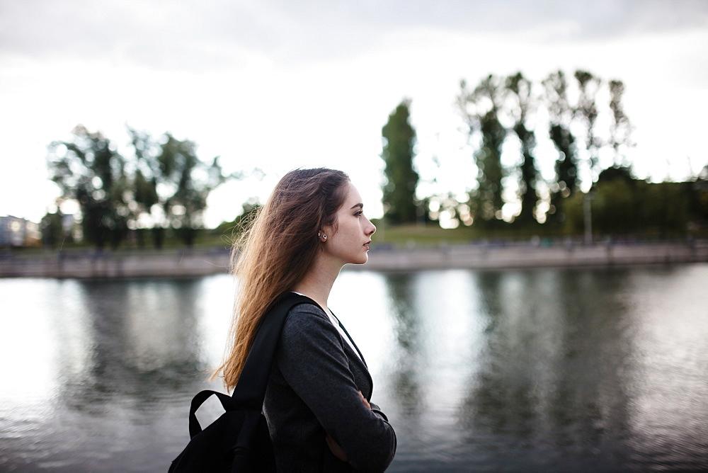 Woman walking near lake in cloudy weather
