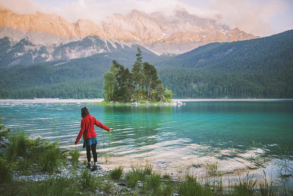Germany, Bavaria, Eibsee, Young woman walking at shore of Eibsee lake in Bavarian Alps - 1178-28749