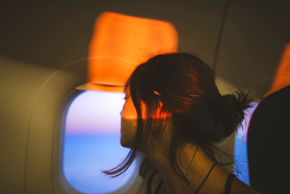 Portrait of young woman in plane illuminated with sunset light