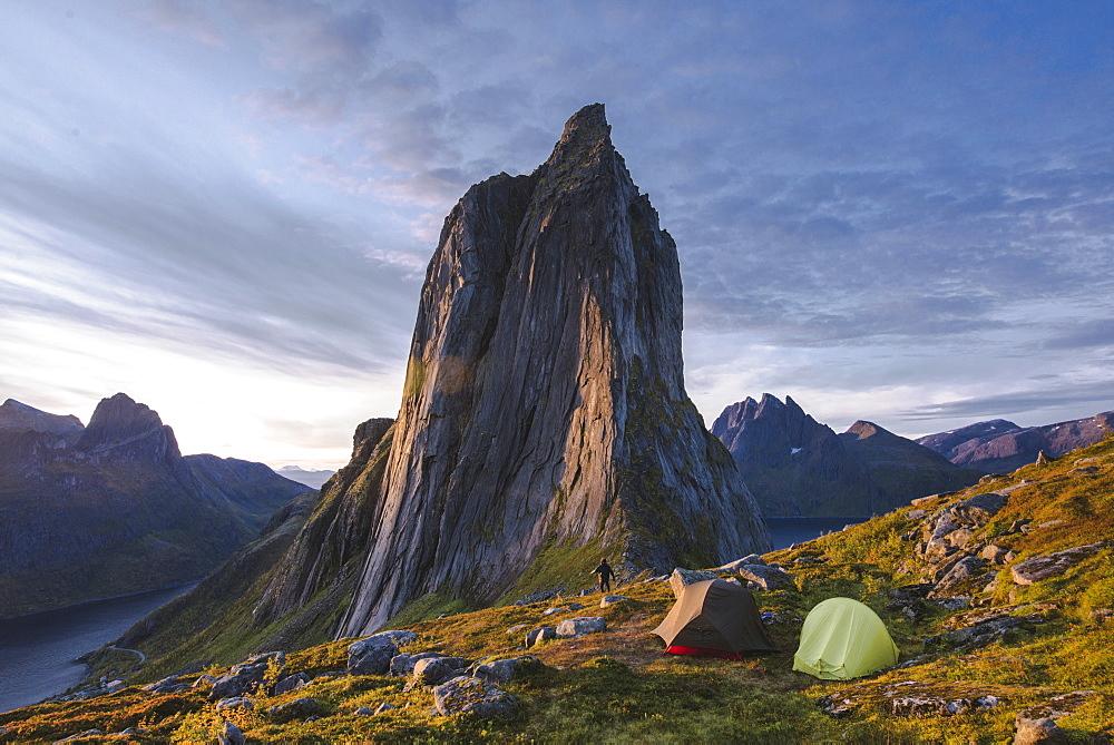 Norway, Senja, Man and two tents near Segla mountain at sunset