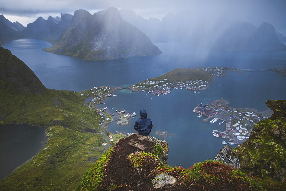 Norway, Lofoten Islands, Reine, Man looking at fjord from Reinebringen mountain during rain