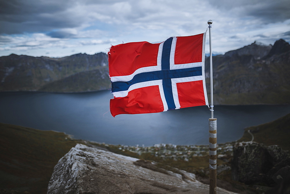 Norway, Senja, Norwegian flag with fjord and mountains in background