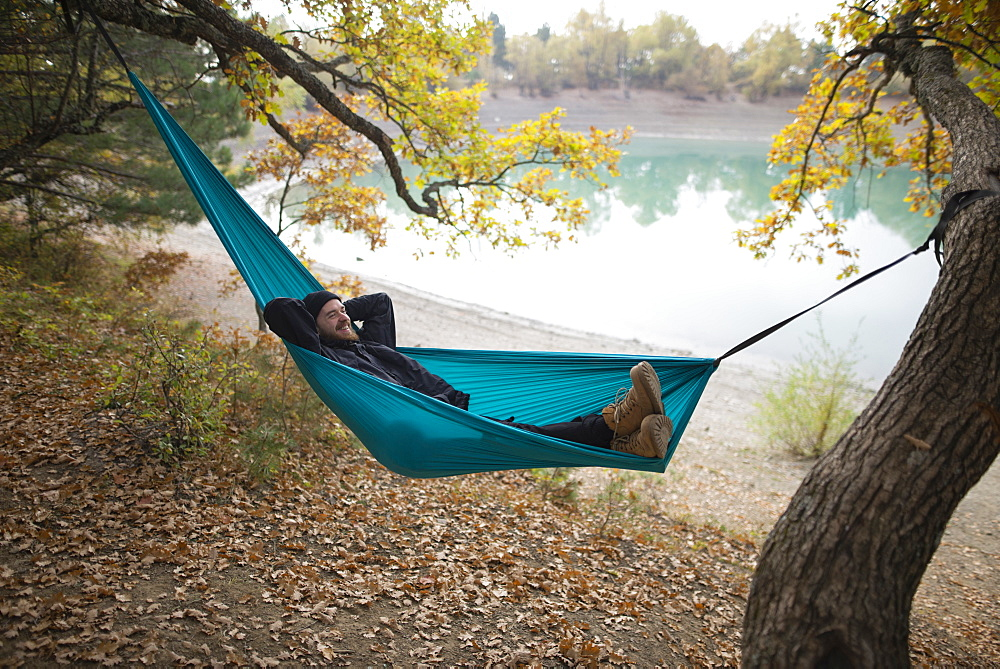 Italy, Smiling man lying in hammock near lake