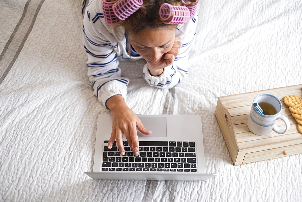 Woman with hair curlers lying on bed and using laptop