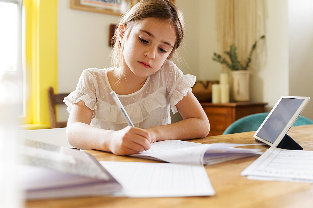 Girl (6-7) working on schoolwork at home