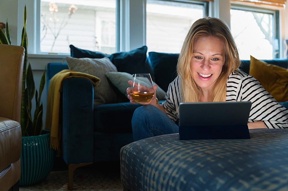 Relaxed woman with wine looking at tablet at home