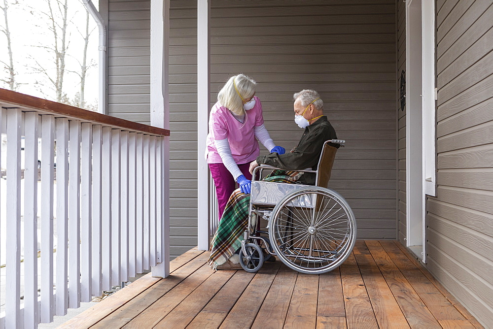 Woman and man in wheelchair wearing protective mask to prevent coronavirus transmission on porch