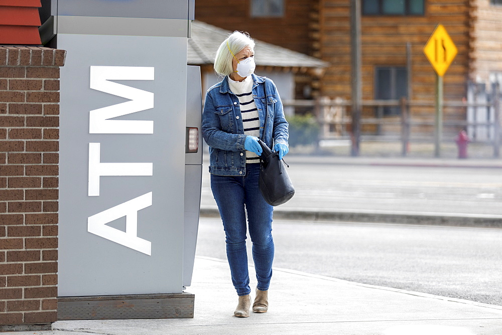Woman wearing gloves and mask to prevent coronavirus transmission at ATM