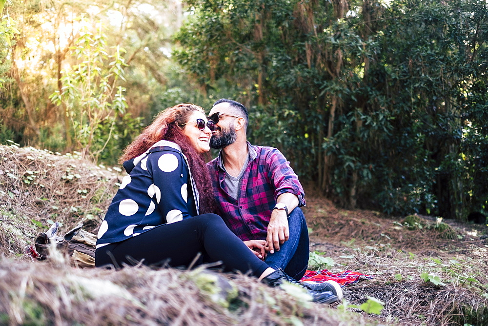 Smiling couple sitting on grass