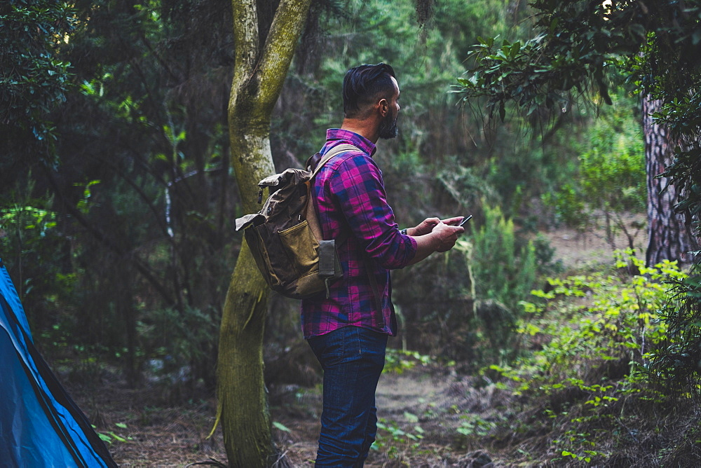 Man wearing backpack using smart phone in forest