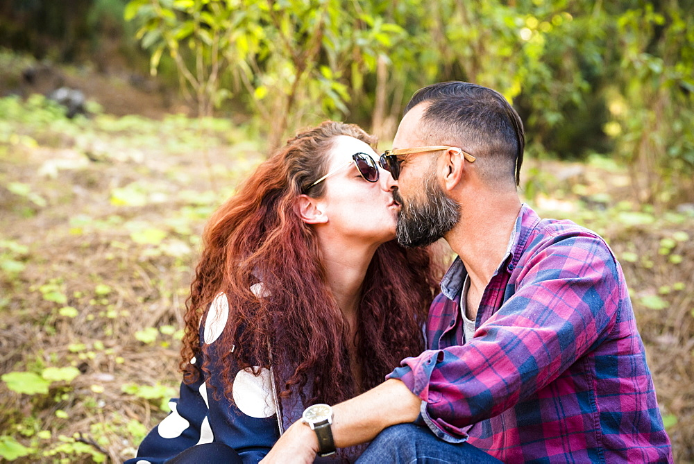 Couple kissing by trees