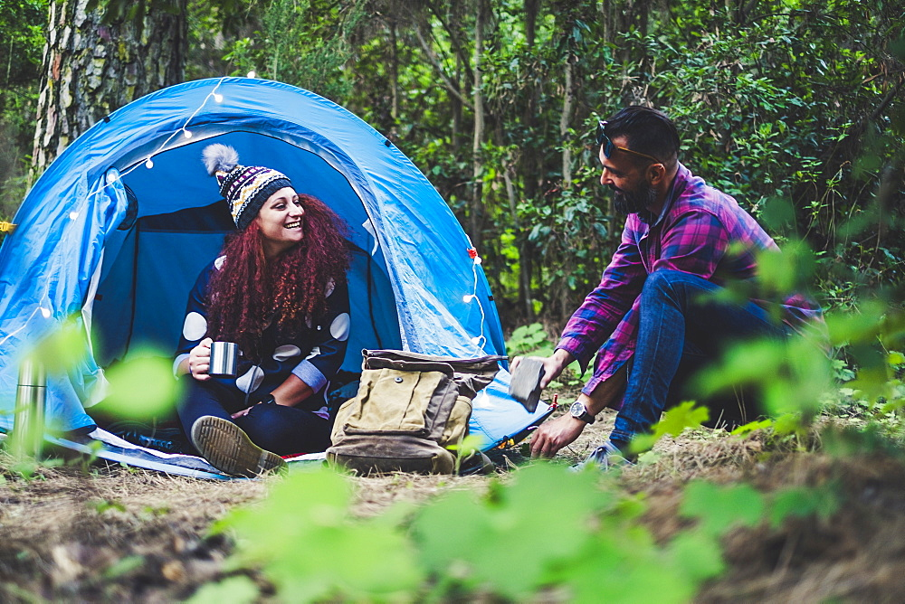Smiling couple camping in forest