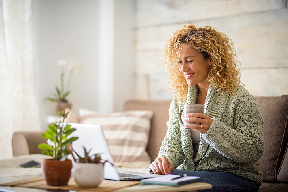 Smiling woman holding drink at laptop