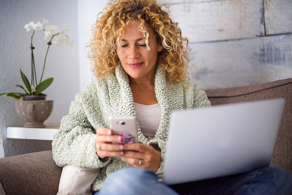 Smiling woman using smart phone and laptop on sofa