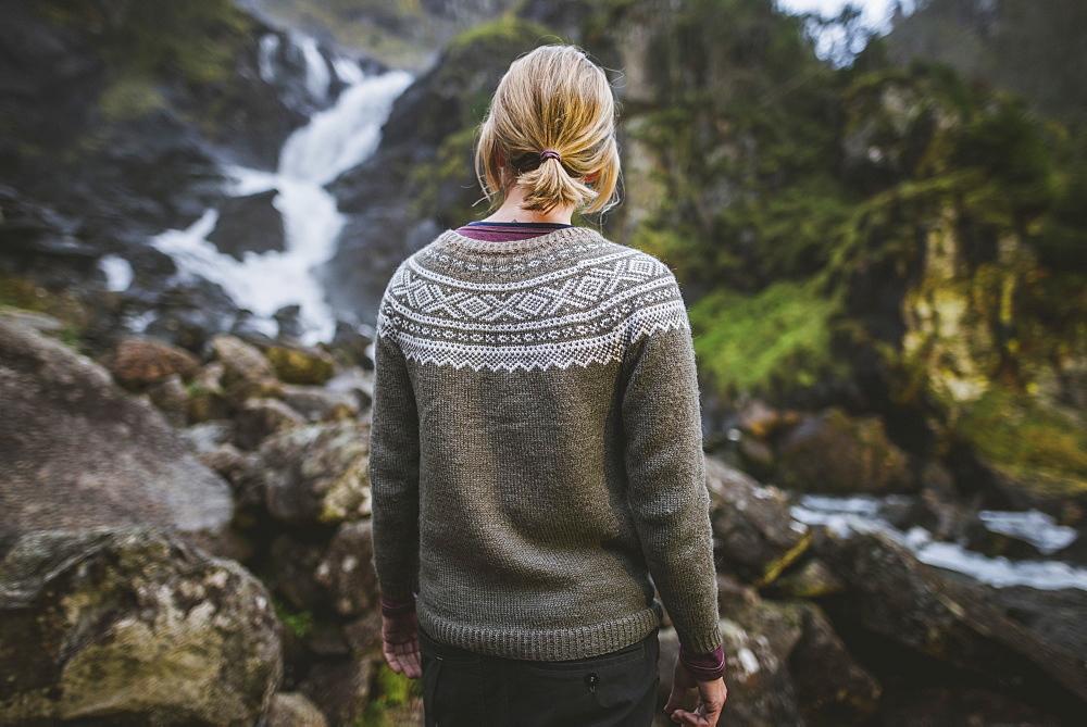 Woman wearing sweater by Latefossen waterfall in Vestland, Norway