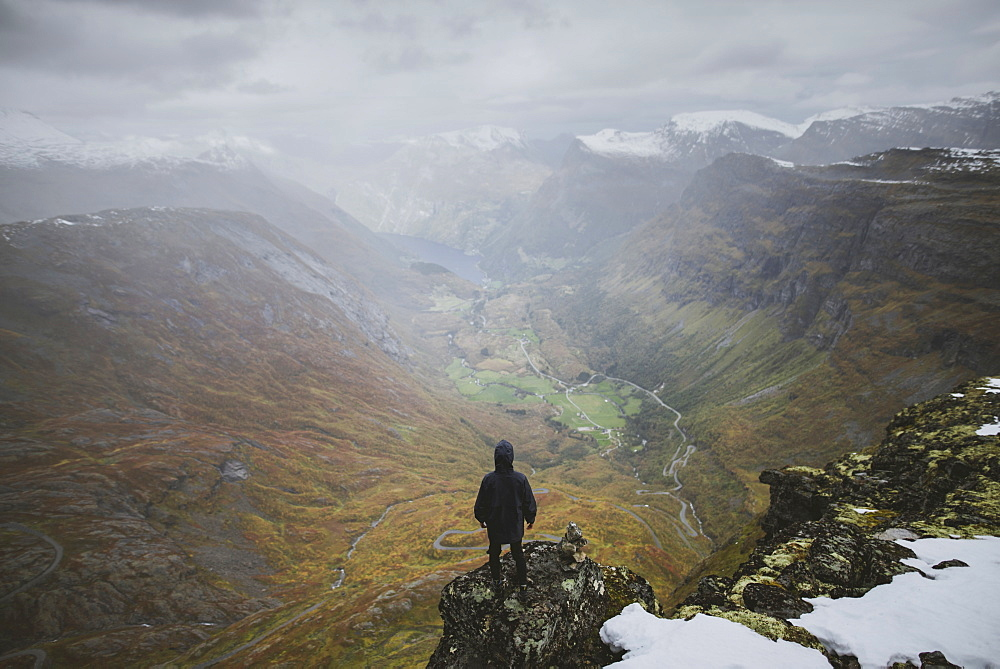 Man standing on Dalsnibba mountain overlooking valley in Geiranger, Norway