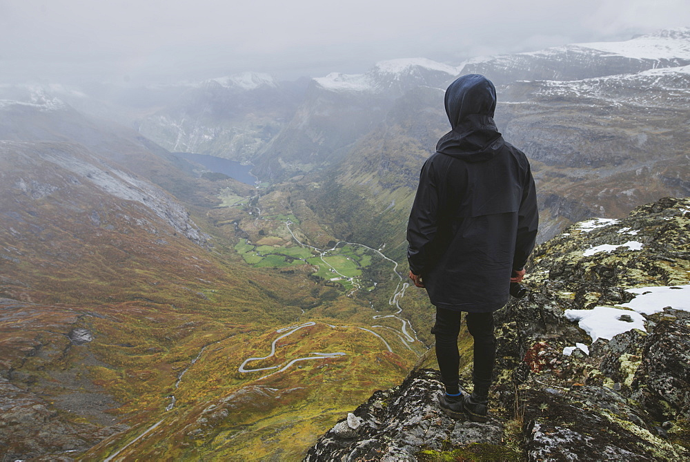 Man holding camera on Dalsnibba mountain overlooking valley in Geiranger, Norway