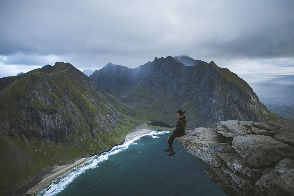 Man sitting on cliff at Ryten mountain in Lofoten Islands, Norway