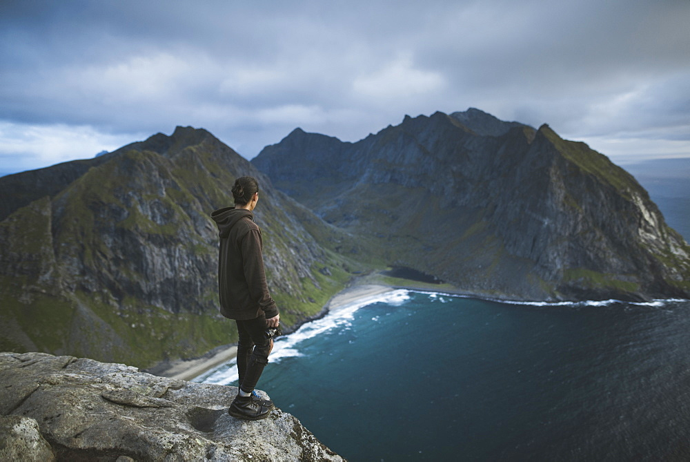 Man holding camera on cliff at Ryten mountain in Lofoten Islands, Norway
