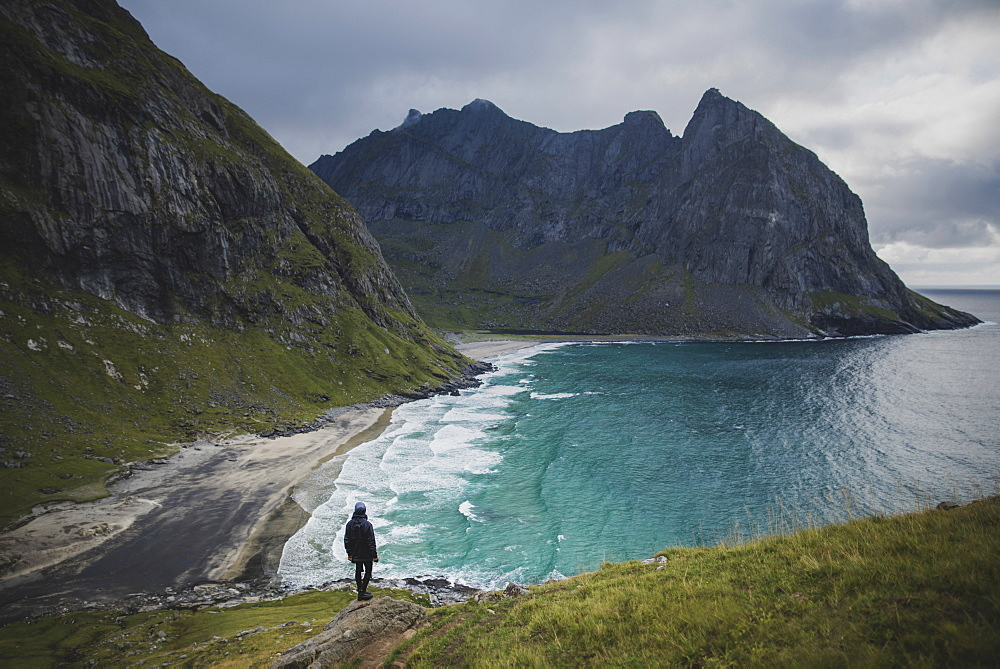 Man standing on rock by Kvalvika Beach in Lofoten Islands, Norway
