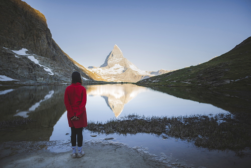 Woman standing by Matterhorn mountain and lake in Valais, Switzerland