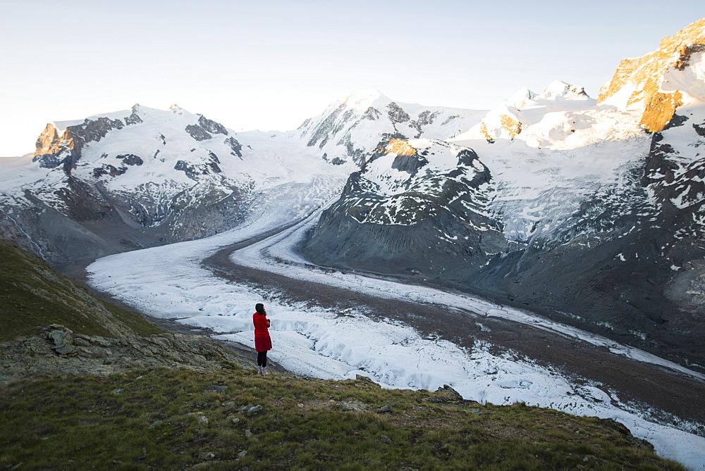 Woman standing on rock by Gorner Glacier in Valais, Switzerland