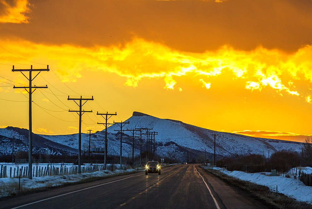 Car on road under dramatic sky at sunrise