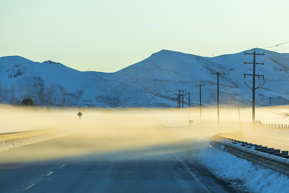 Fog on road by snowy mountains