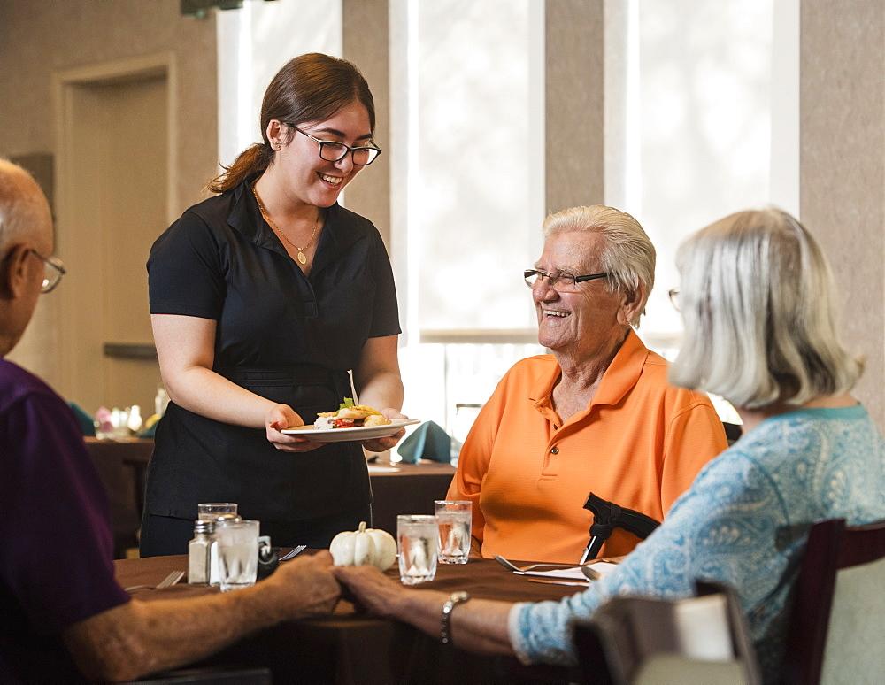 Smiling waitress handing food to smiling senior man