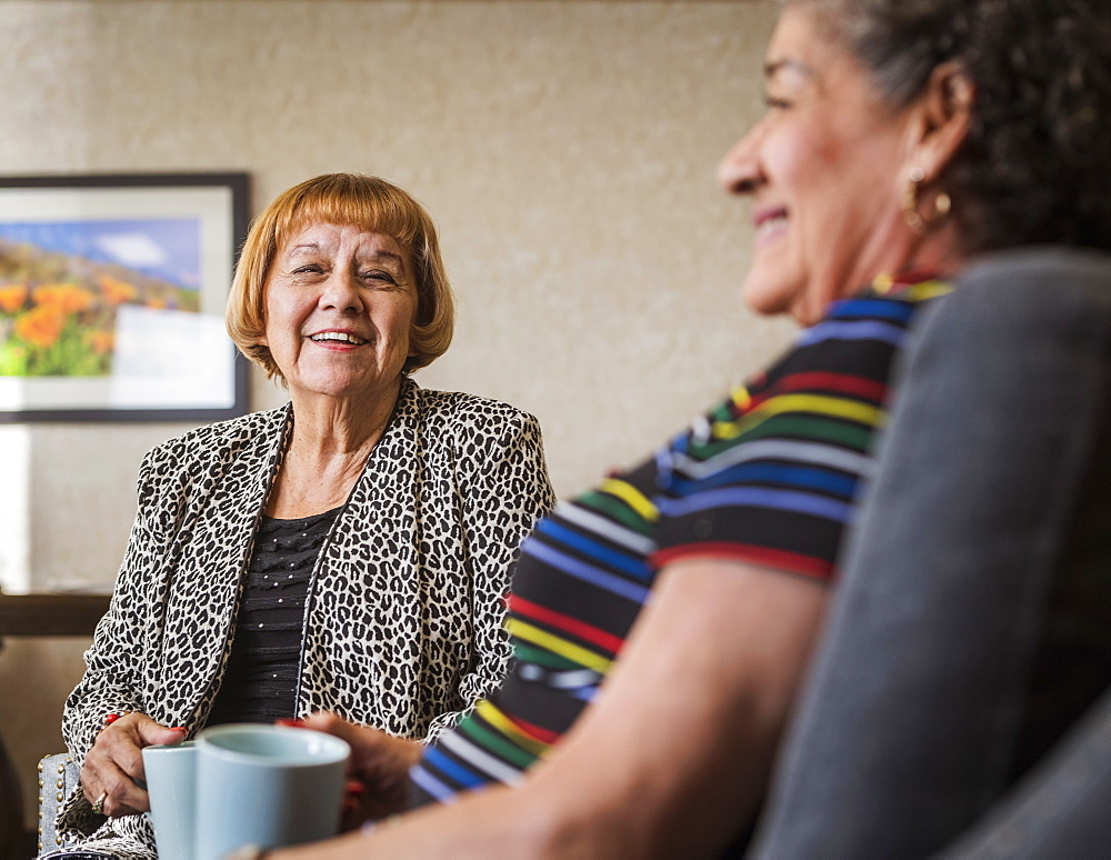 Smiling senior women holding cups