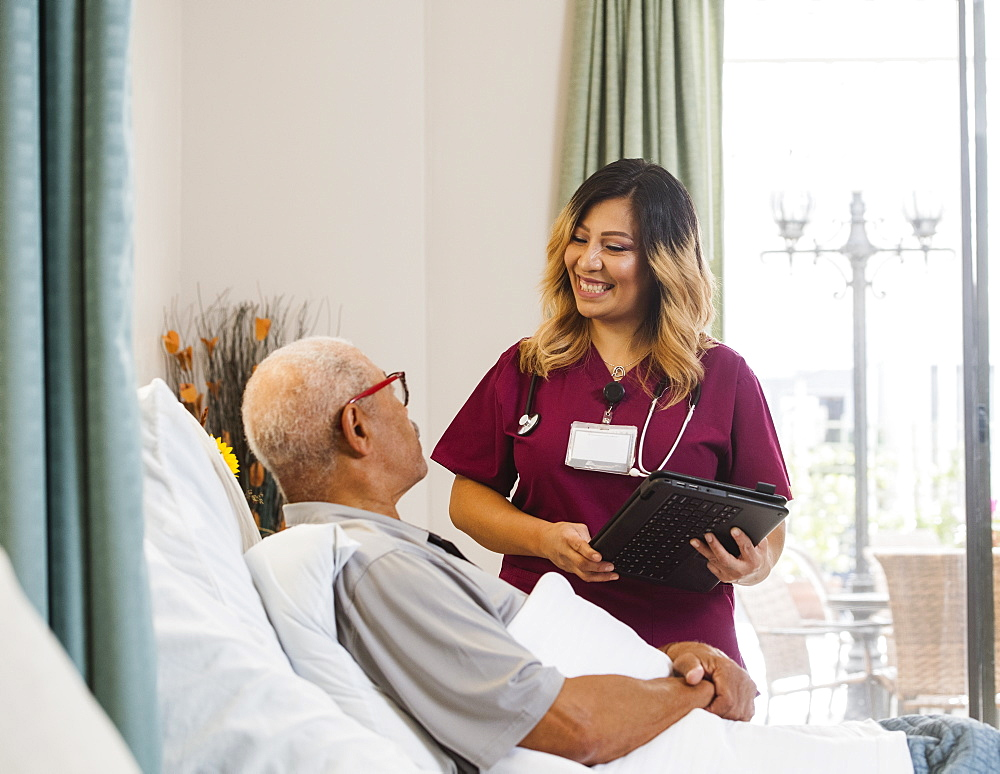 Smiling nurse holding clipboard by senior man in bed