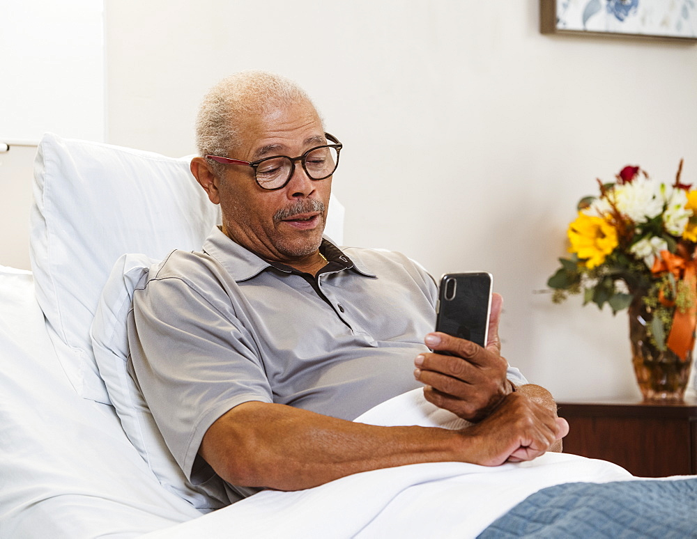 Senior man using smart phone in bed