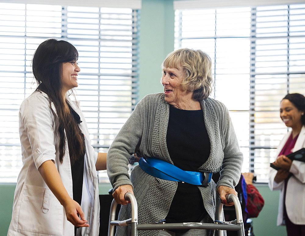Smiling doctor helping senior woman use walking frame