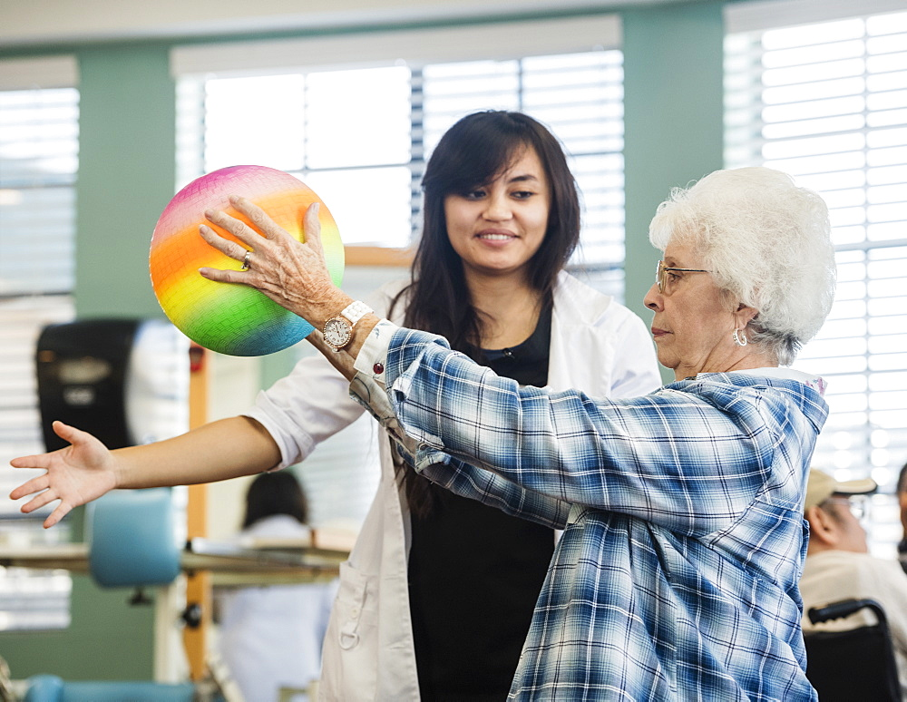Senior woman holding ball at rehabilitation center
