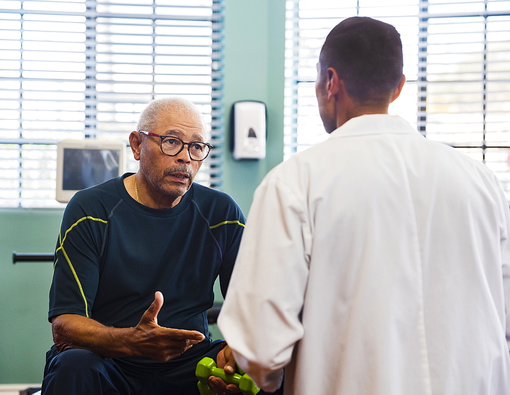 Senior man talking to doctor at rehabilitation center