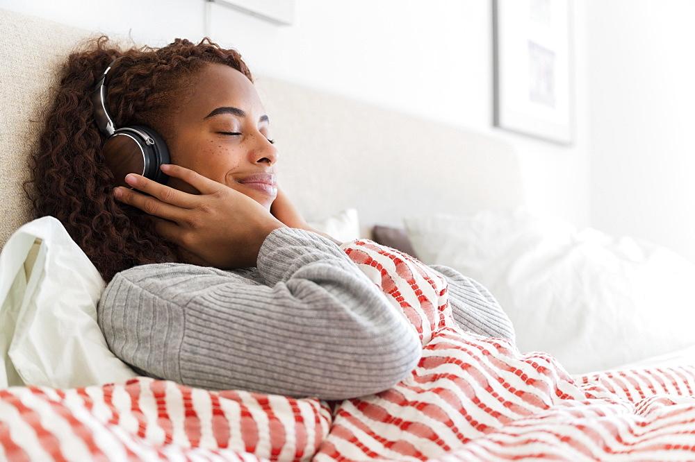 Smiling woman wearing headphones in bed