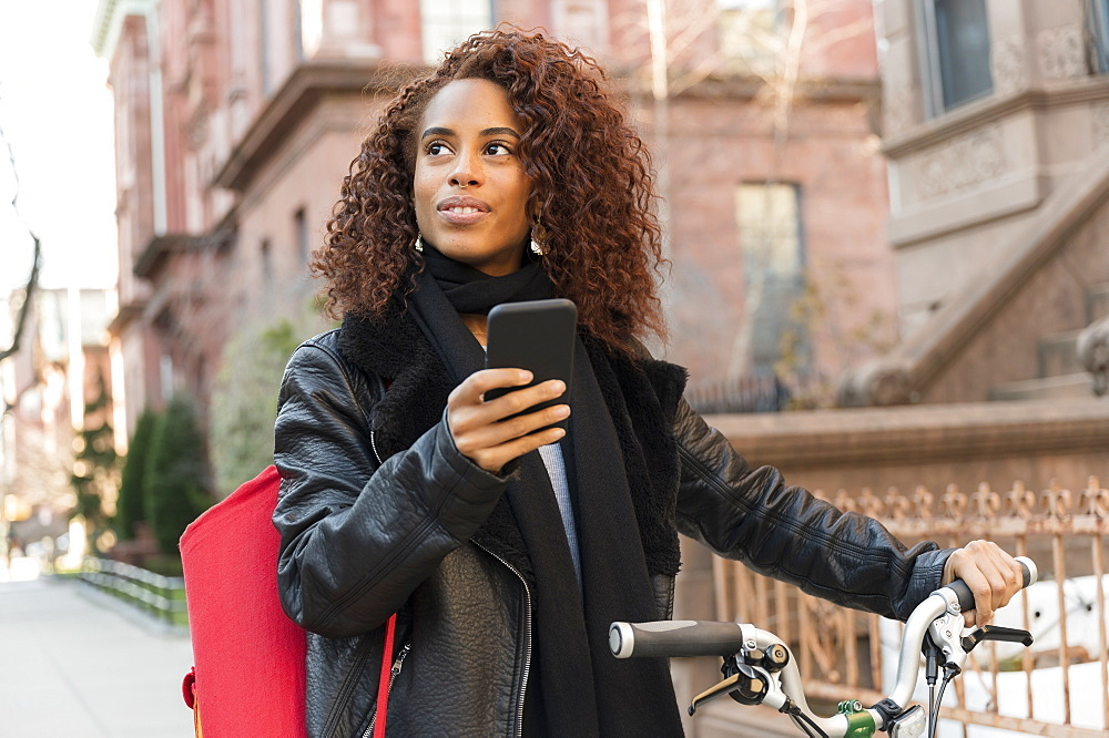 Woman holding smart phone and bicycle in city