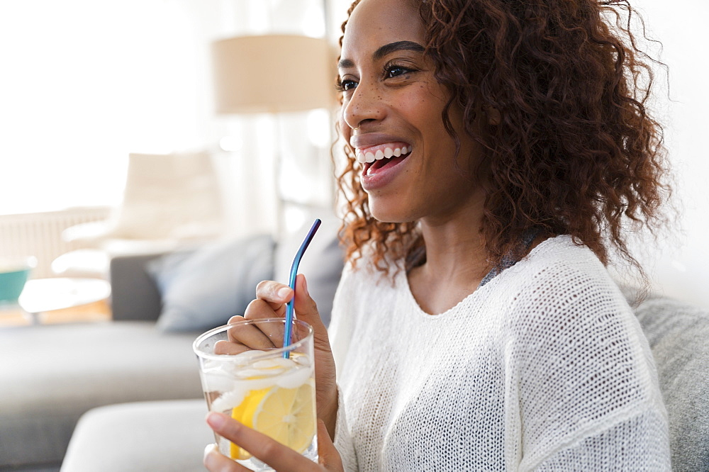 Smiling woman holding drink with straw